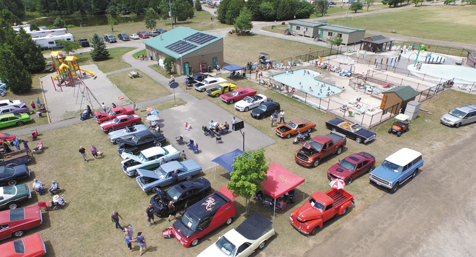 Car show by pool and splash pad